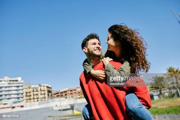 happy young man giving girlfriend a piggyback ride - sobre os ombros - fotografias e filmes do acervo