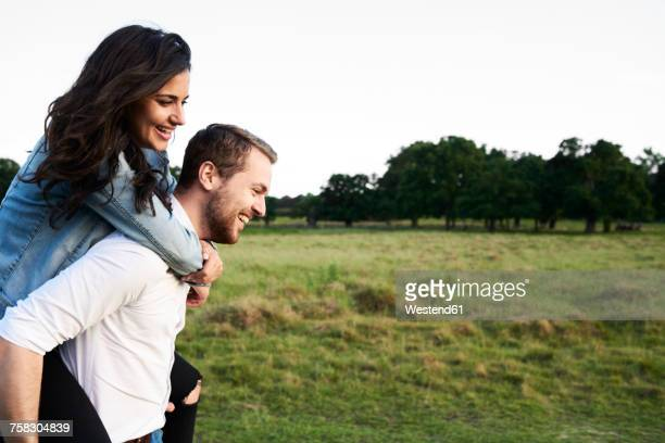 happy young man giving his girlfriend a piggyback ride - sobre os ombros - fotografias e filmes do acervo