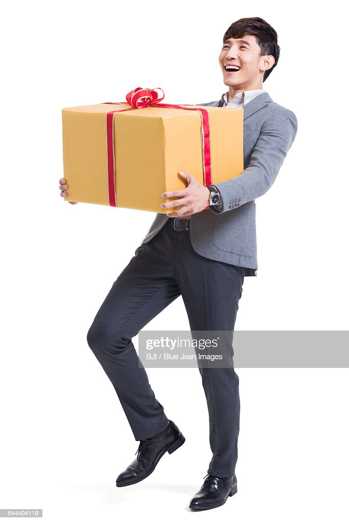 Hy Young Man Holding A Large Gift Stock Photo