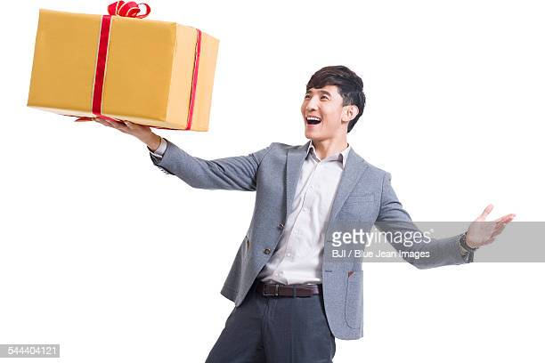 Happy young man holding a large gift
