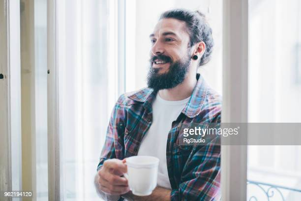 happy young man holding coffee cup - man bun stock pictures, royalty-free photos & images