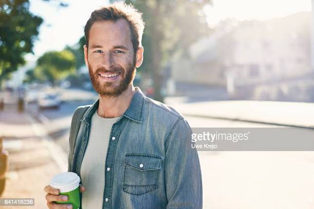 happy young man holding disposable cup on street - waist up stock pictures, royalty-free photos & images