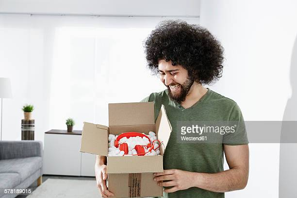 Happy young man holding packet with his new headphones