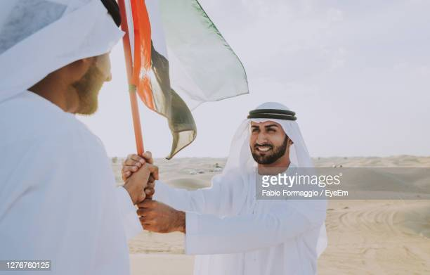 happy young man holding woman standing against the sky - gulf countries stock-fotos und bilder
