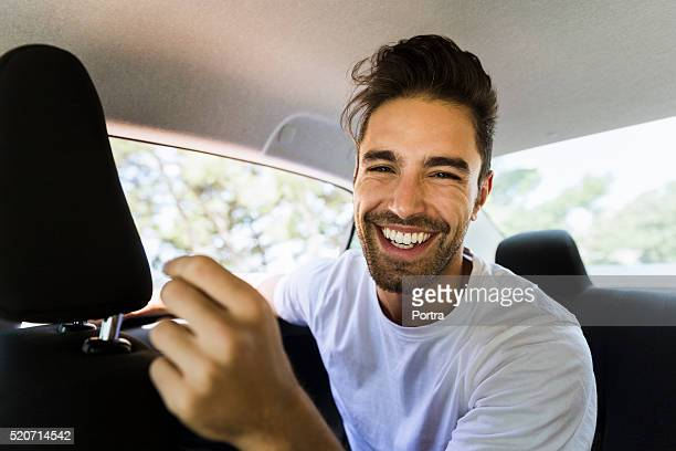 happy young man in car - 25 29 jaar stockfoto's en -beelden