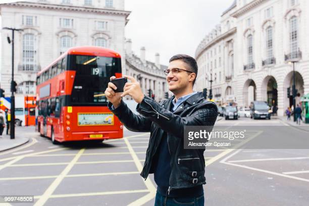 Happy young man in eyeglasses taking pictures with smart phone at Piccadilly Circus in London, England, UK