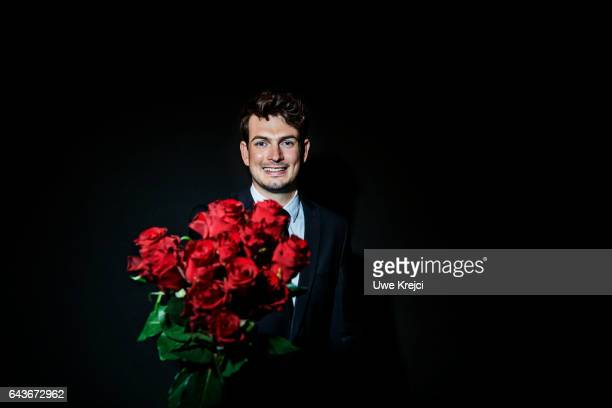 Happy young man in suit holding red roses