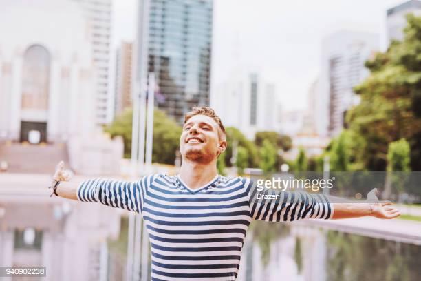 gelukkig jonge man in de stad met uitgestrekte armen - moeiteloos stockfoto's en -beelden