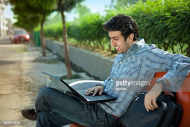 Happy young man is on park chair using laptop computer.