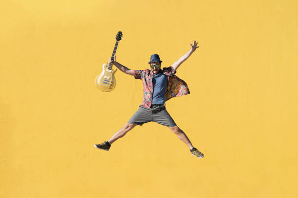 Happy young man jumping with an yellow electric guitar and playing pop music