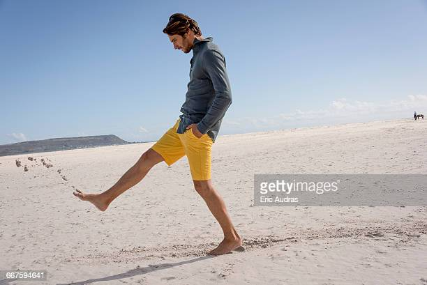 Happy young man kicking sand on beach