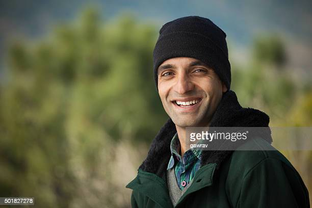 Happy young man looking at camera in winter outdoor scene.