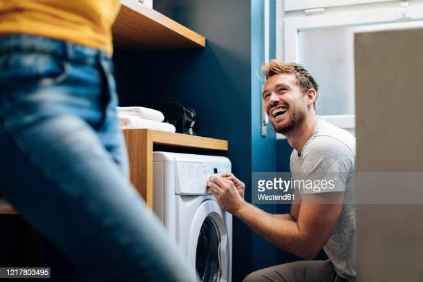 happy young man looking at girlfriend and doing the laundry at home - waschmaschine stock-fotos und bilder