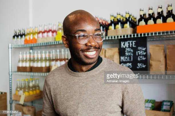 happy young man looking away at coffee shop - one man only stock pictures, royalty-free photos & images