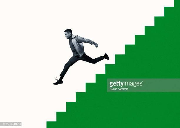 happy young man moving down on green steps - zweifarbig farbe stock-fotos und bilder