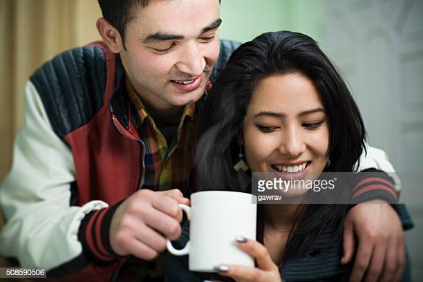 Happy young man offering coffee to his wife.