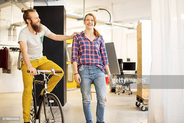 Happy young man on bicycle with female colleague