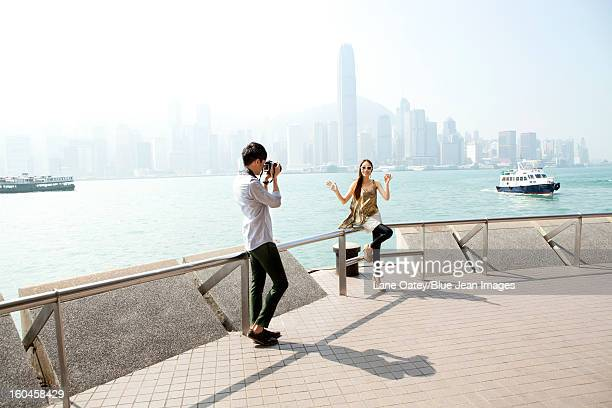 Happy young man photographing young women with SLR camera in Victoria Harbor, Hong Kong