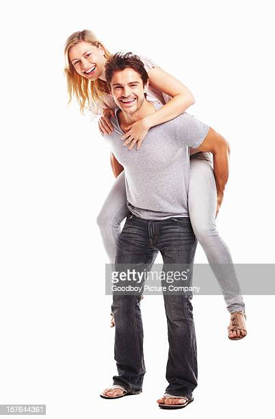 Happy young man piggybacking his partner against white