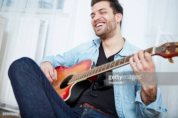 happy young man playing guitar - classical guitar stock photos and pictures