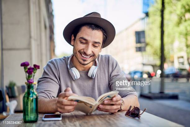 happy young man reading book at outdoors cafe - eastern european stock pictures, royalty-free photos & images