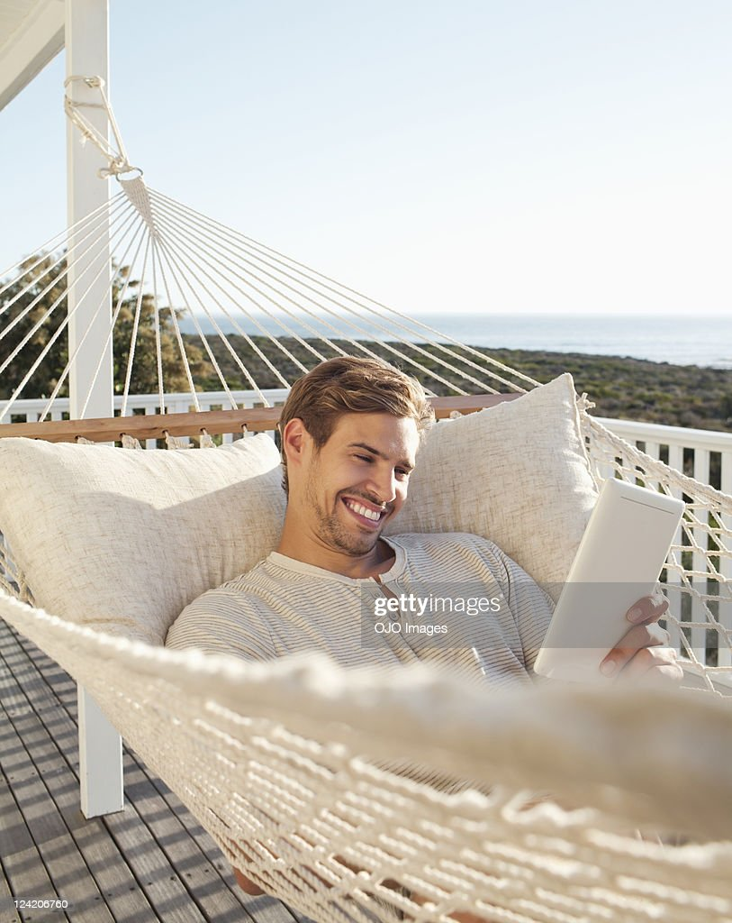 Happy young man reading electronic book in hammock : Stock Photo
