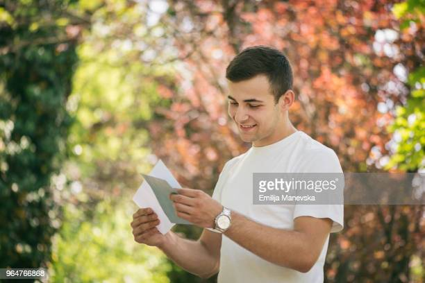 happy young man receiving letter - receiving stock pictures, royalty-free photos & images