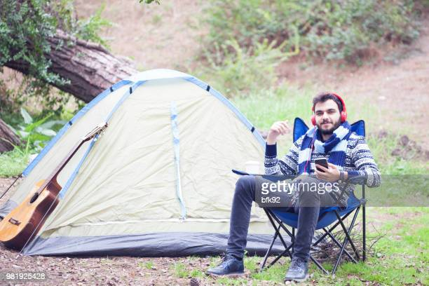 Happy young man relaxing in camping area and reading a book.