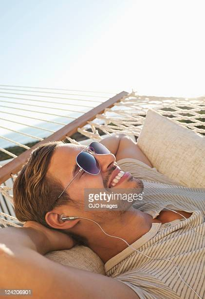 Happy young man relaxing in hammock and listening to music