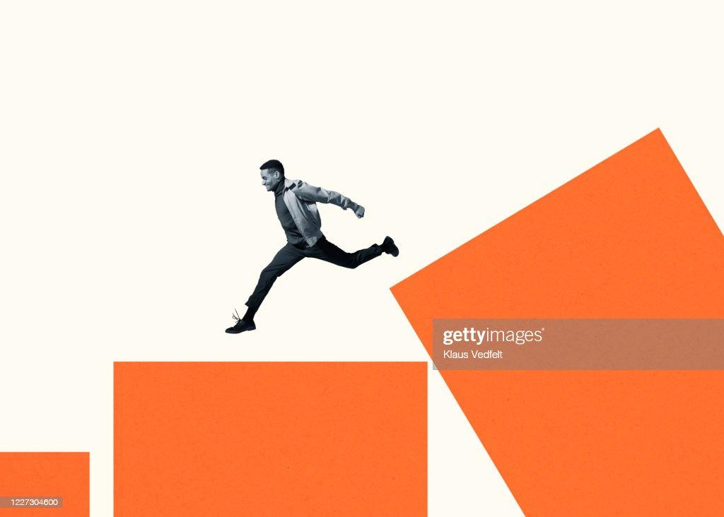 Happy young man running on large orange bar graph : Stock Photo