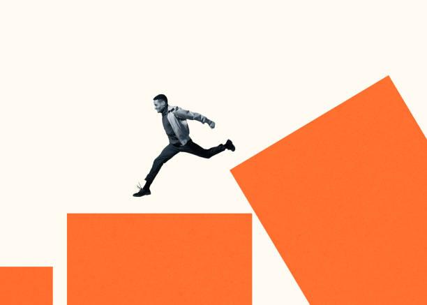 Happy young man running on large orange bar graph