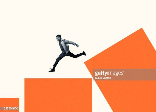 happy young man running on large orange bar graph - jumping stock pictures, royalty-free photos & images