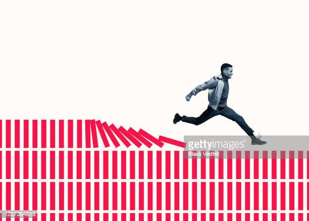 happy young man running on red columns - development stock pictures, royalty-free photos & images