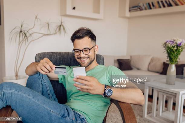 happy young man shopping online at home - credit card stock pictures, royalty-free photos & images