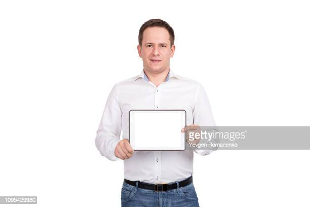 Happy young man showing blank tablet computer screen over white background. Looking at camera