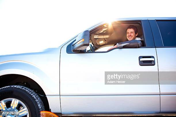 Happy young man sitting in pickup truck