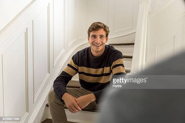 Happy young man sitting on steps