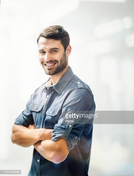 happy young man standing arms crossed in office - braços cruzados imagens e fotografias de stock