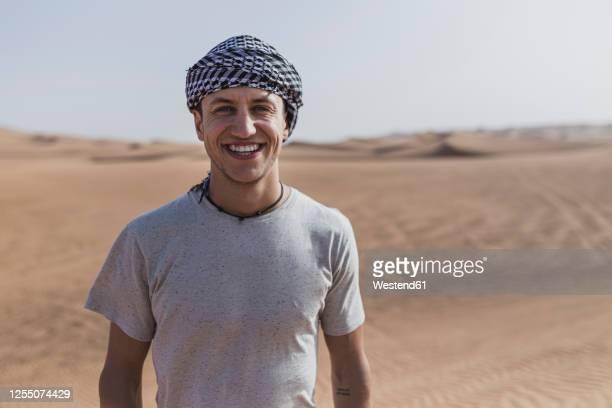 happy young man standing at desert in dubai, united arab emirates - paisajes de emiratos arabes fotografías e imágenes de stock