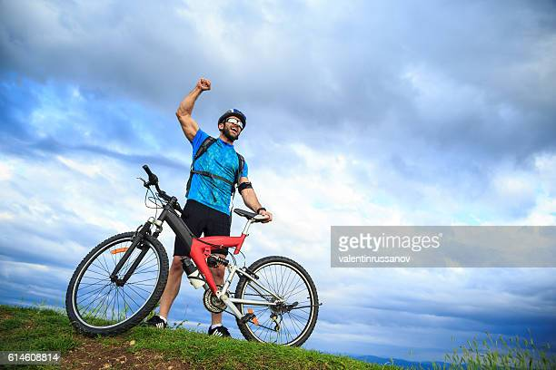 Happy young man standing hand up on top mountain