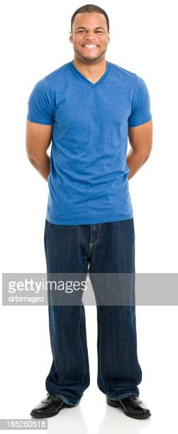 Happy Young Man Standing With Arms Behind Back