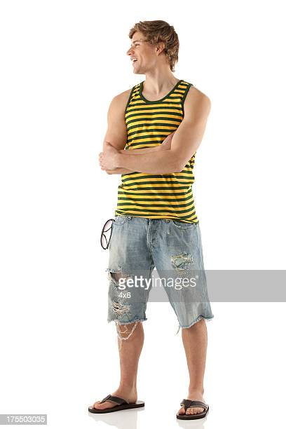 Happy young man standing with his arms crossed