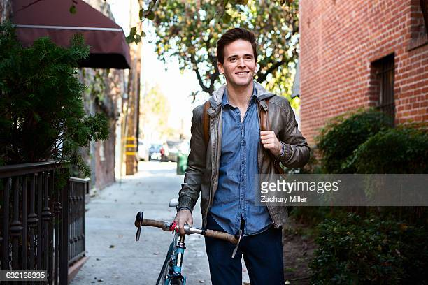 happy young man strolling with cycle on sidewalk - monrovia california stock pictures, royalty-free photos & images