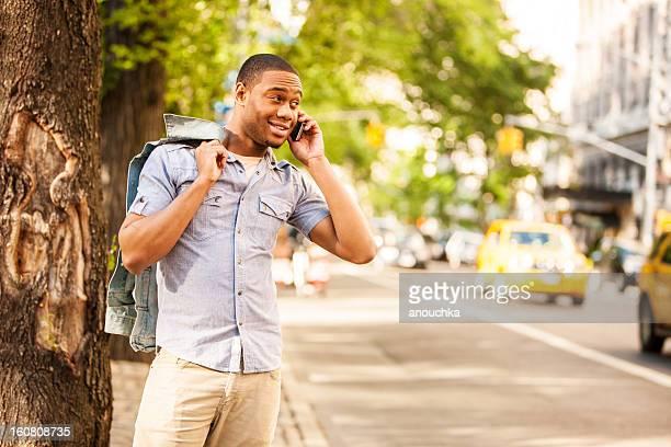 幸せな若い男の携帯電話を屋外で使って