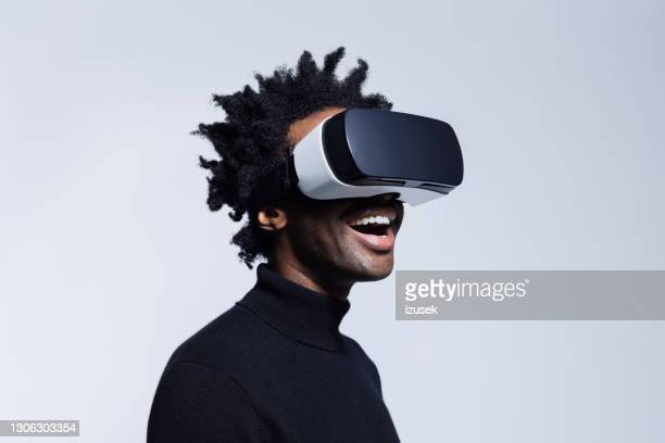 happy young man using virtual reality glasses - african american culture stock pictures, royalty-free photos & images