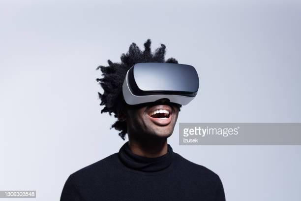 jovem feliz usando óculos de realidade virtual - izusek - fotografias e filmes do acervo