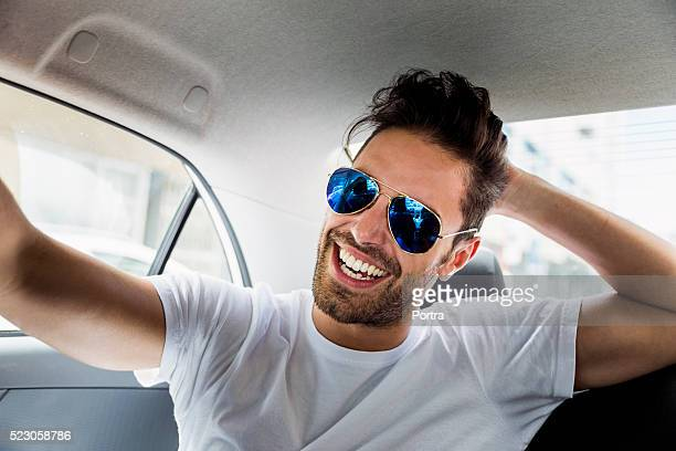 Happy young man wearing sunglasses in car