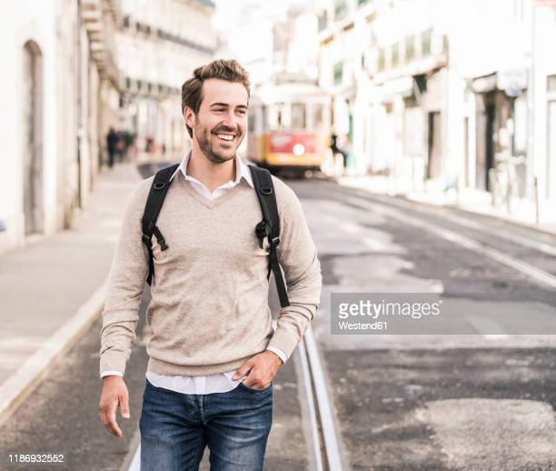 happy young man with backpack in the city on the go, lissabon, portugal - sorriso aberto imagens e fotografias de stock