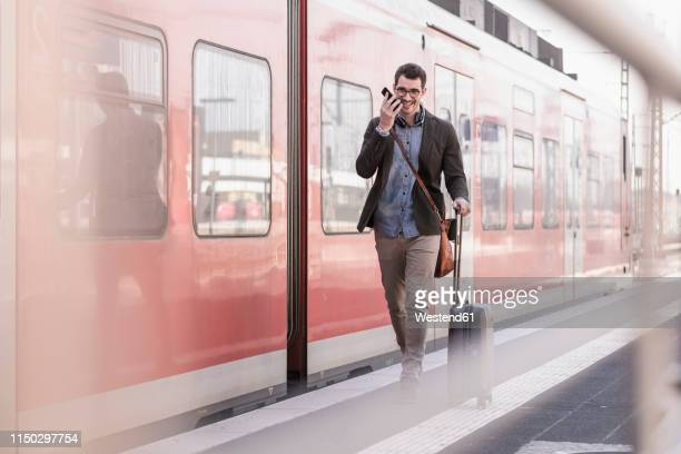 happy young man with cell phone walking on station platform along commuter train - bahnreisender stock-fotos und bilder