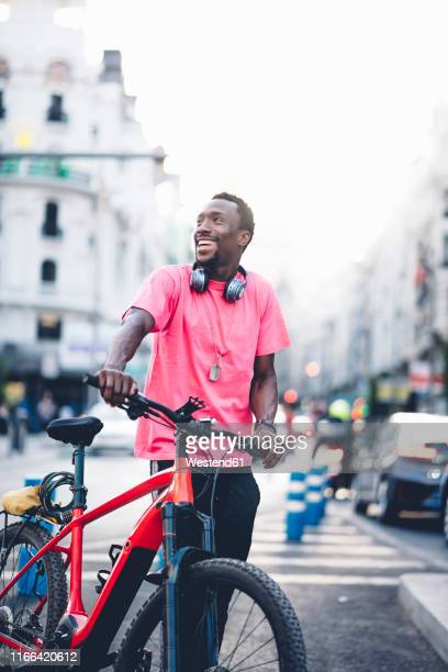 happy young man with e bike in the city - bicycle messenger stock pictures, royalty-free photos & images